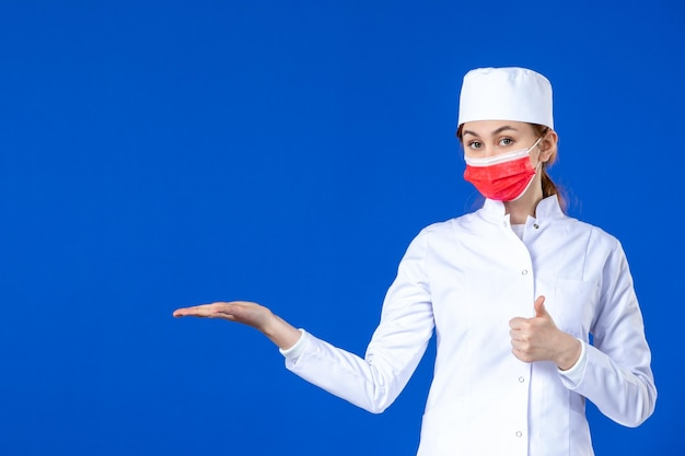 Front view of young nurse in medical suit with red mask on blue