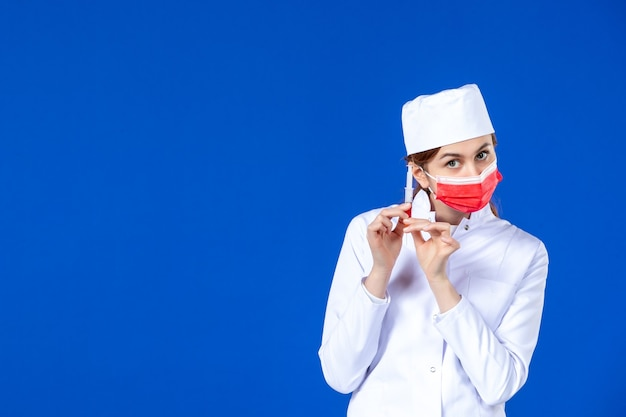 Giovane infermiera di vista frontale in vestito medico con maschera rossa e iniezione nelle sue mani sulla parete blu