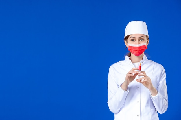 Front view young nurse in medical suit with red mask and injection in her hands on blue wall