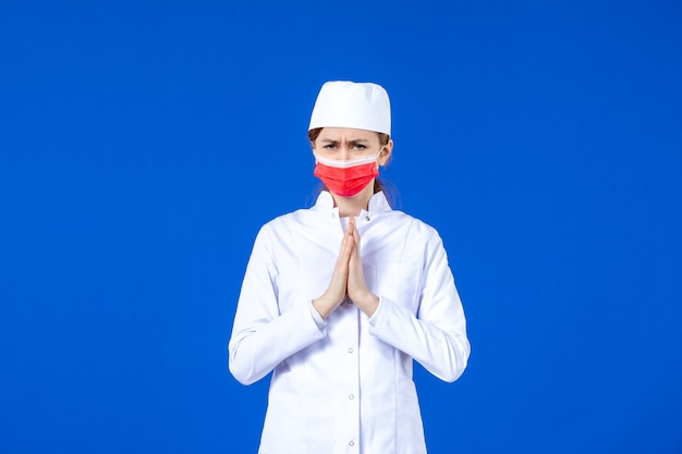 Front view young nurse in medical suit with red protective mask on blue wall