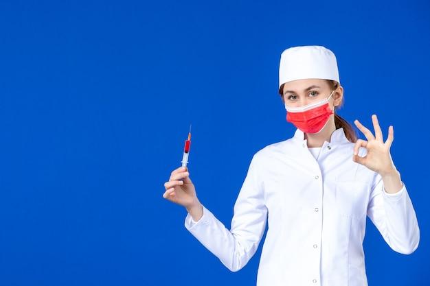 Giovane infermiera di vista frontale in vestito medico bianco con maschera rossa e iniezione nelle sue mani sulla parete blu