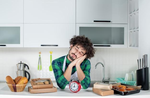 Vista frontale del giovane uomo troppo stanco in piedi dietro l'orologio da tavolo vari pasticcini nella cucina bianca