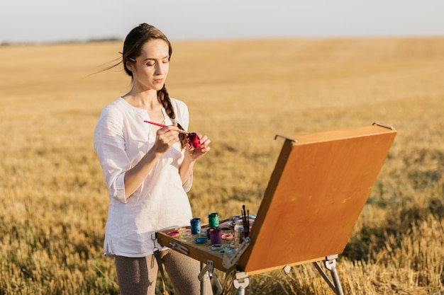 Front view young painter in the nature