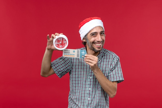 Front view young person holding ticket and clock on light red wall red male emotion time