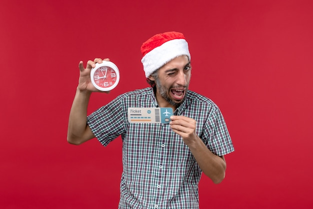 Front view young person holding ticket and clock on a red wall red emotion time male