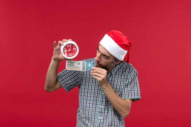 Front view young person holding ticket and clock on red wall red male emotions time