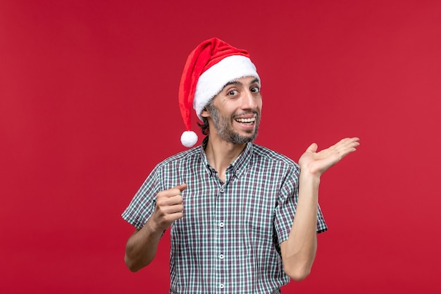 Front view young person with excited expression on red wall holiday new year male red
