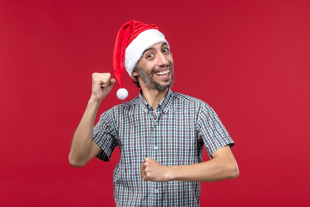 Front view young person with excited expression on a red wall red new year holiday male