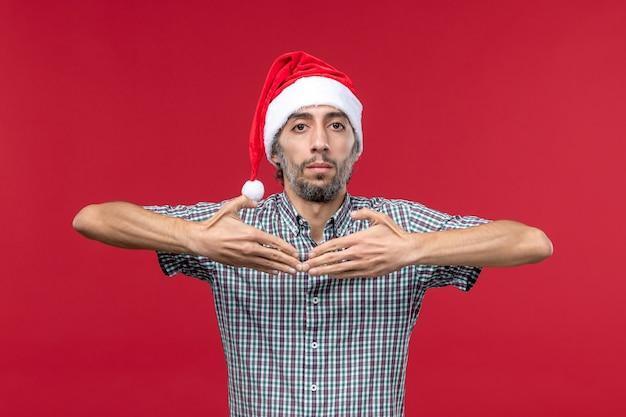 Вид спереди молодой человек в новогодней шапке на красном столе новогодние красные праздники самца
