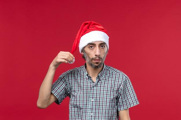 Вид спереди молодой человек в новогодней шапке на красной стене новогодние красные праздники