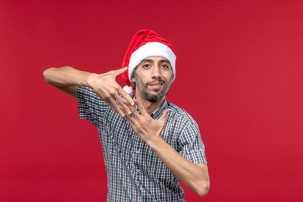 赤い壁に新年のキャップを持つ正面図若い人赤い年末年始男性