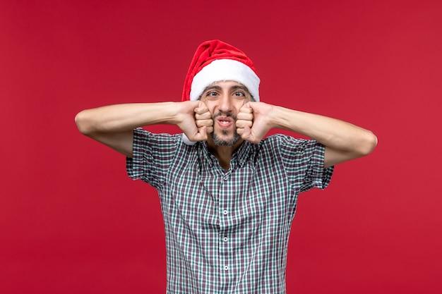 赤い壁に新年のキャップを持つ正面図若い人赤い新年の休日の男性