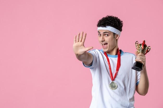 Вид спереди молодой игрок в спортивной одежде с золотой чашкой на розовой стене