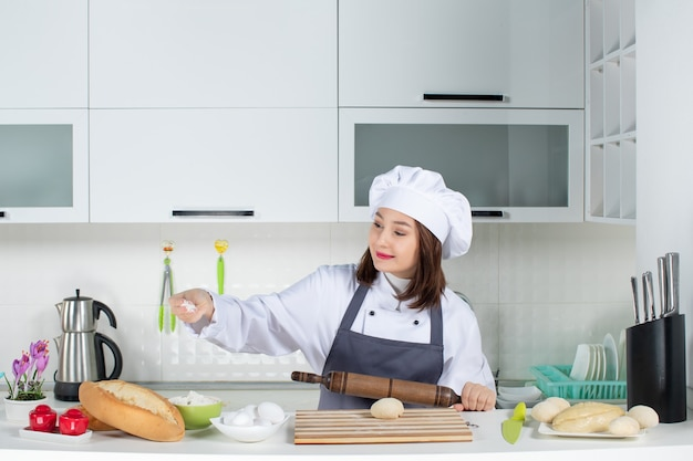 Front view of young positive female chef in uniform standing behind table preparing pastry in the white kitchen