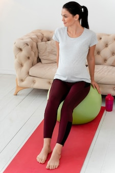 Front view young pregnant woman exercising on fitness ball