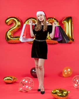 Front view young pretty female in black dress holding shopping bags balloons on red