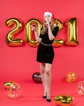 Vista frontale giovane bella donna in abito nero che fa segno shh palloncini su rosso