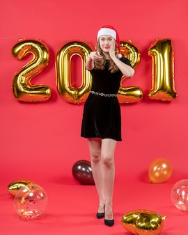 Front view young pretty female in black dress pointing at camera balloons on red