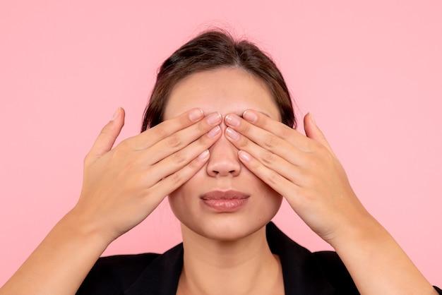 Vista frontale giovane donna graziosa che copre gli occhi su sfondo rosa