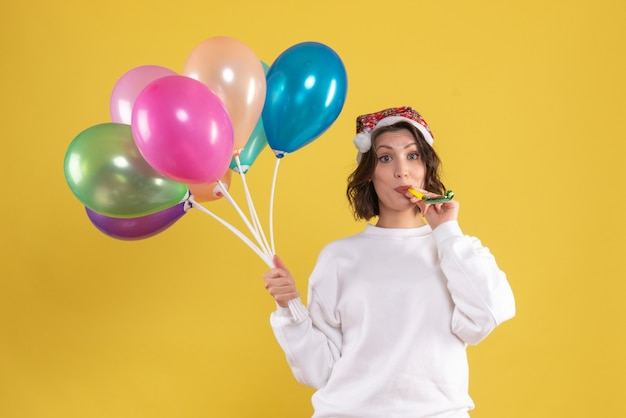 Front view young pretty female holding balloons on a yellow new year emotion christmas color woman