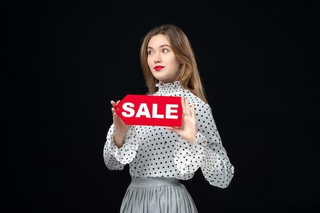 Vista frontale giovane bella donna che tiene la scrittura in vendita rossa sul muro nero shopping foto moda donna emozione