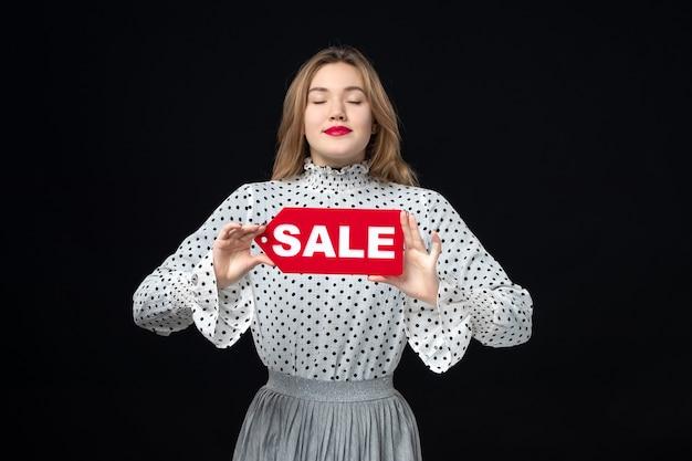 正面図若いきれいな女性が赤い販売を保持している黒い壁の色のショッピングファッション写真の感情に書き込みます