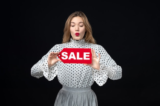 正面図若いきれいな女性が赤い販売を保持している黒い壁の色のショッピングファッション女性の感情に書き込みます
