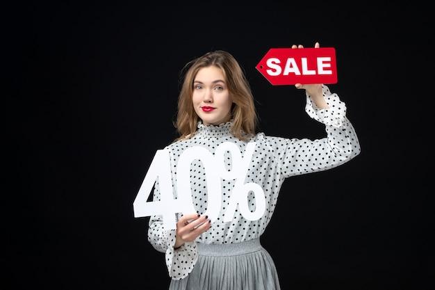 판매 글과 검은 벽 색상 쇼핑 휴가 크리스마스 감정 패션을 들고 전면 보기 젊은 예쁜 여성