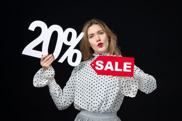 Вид спереди молодая симпатичная женщина, держащая распродажу, написание и на черном фоне, модель эмоции, шоппинг женщина, красота, цвет, мода