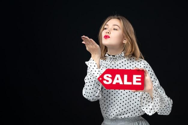 正面図若いきれいな女性が販売を保持し、黒い壁の色のショッピング写真の女性の感情の赤いファッションにキスを書いて送信します