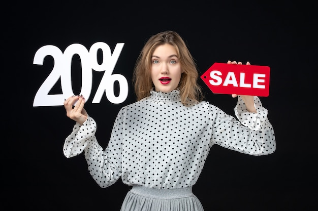 Front view young pretty female holding sale writing and on black background woman model emotion beauty color fashion