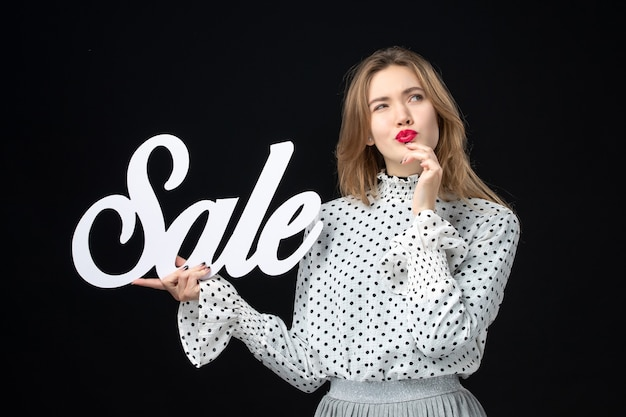 Front view young pretty female holding sale writing on black wall beauty emotion color model photo fashion