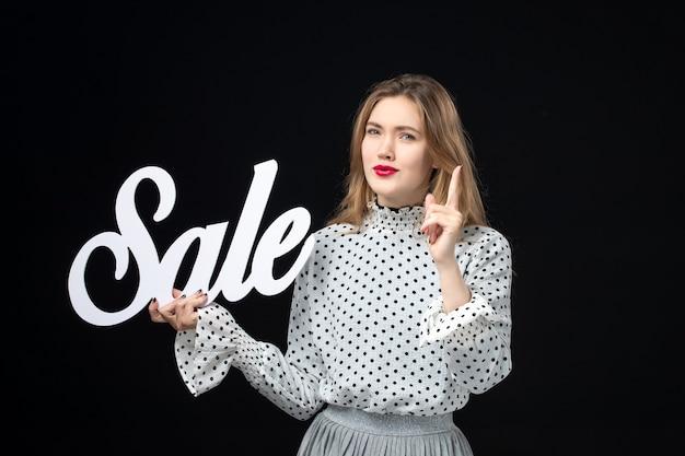 Vista frontale giovane bella donna che tiene in vendita la scrittura sul muro nero colore shopping modello di bellezza foto di moda emozione