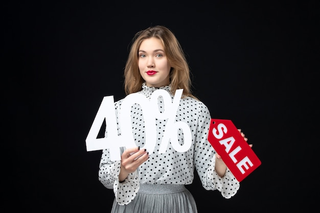Front view young pretty female holding sale writing and on black wall color shopping fashion holiday xmas emotion