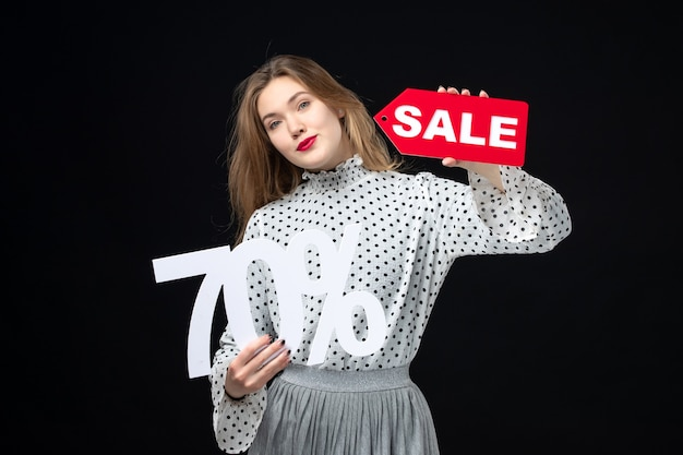 Front view young pretty female holding sale writing and on black wall color shopping fashion photo emotion beauty model xmas