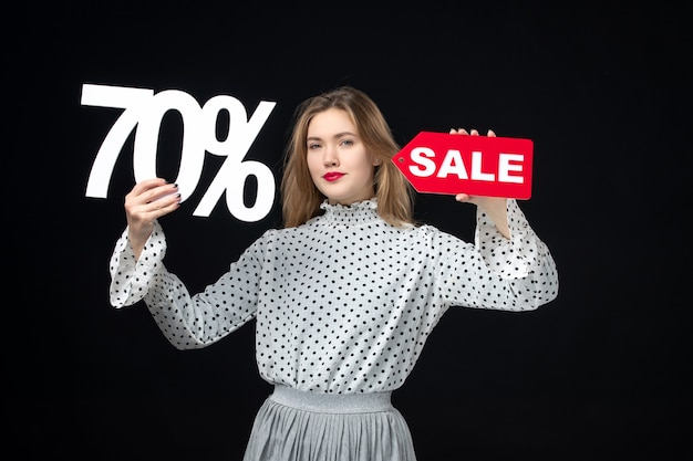 Front view young pretty female holding sale writing and on black wall color shopping fashion photo emotion model xmas
