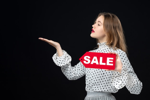 Front view young pretty female holding sale writing on a black wall color shopping photo woman emotion red fashion