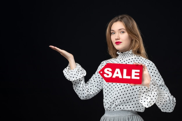 Front view young pretty female holding sale writing on black wall color shopping photo woman emotion red fashion