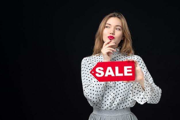 Vista frontale giovane bella donna che tiene vendita scrivendo sul muro nero emozione rosso shopping foto moda donna colori