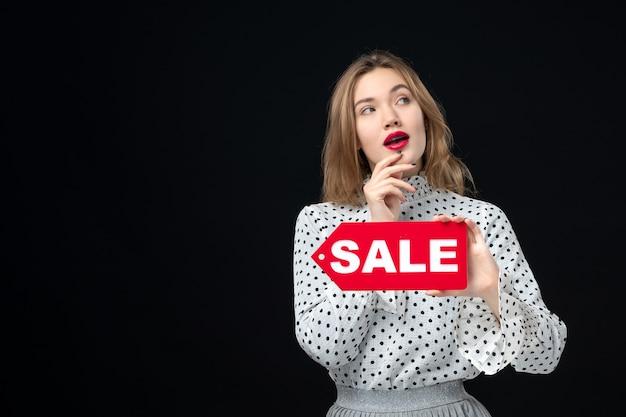Vista frontale giovane bella donna che tiene vendita scritta sul muro nero emozione rosso shopping foto donna colore
