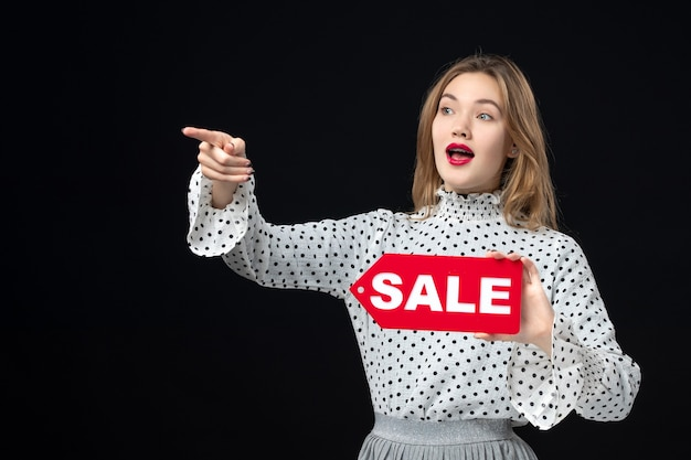 Front view young pretty female holding sale writing on black wall model beauty emotion shopping fashion woman color red