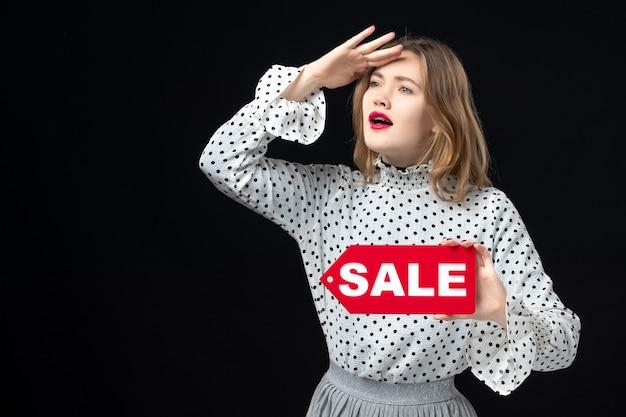 Vista frontale giovane bella donna che tiene vendita scritta sul muro nero modello bellezza emozione shopping moda donna color