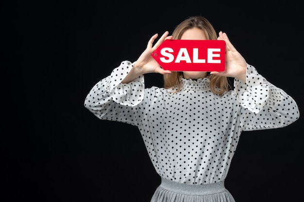 Front view young pretty female holding sale writing on black wall model beauty emotion shopping woman color