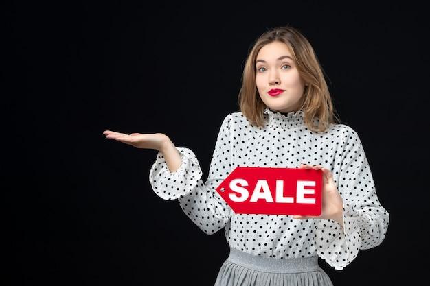 Vista frontale giovane bella donna che tiene la vendita scritta sul muro nero modello bellezza shopping moda donna colore