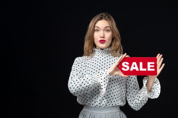 Vista frontale giovane bella donna che tiene vendita scritta sul muro nero modello emozione shopping moda donna bellezza colore