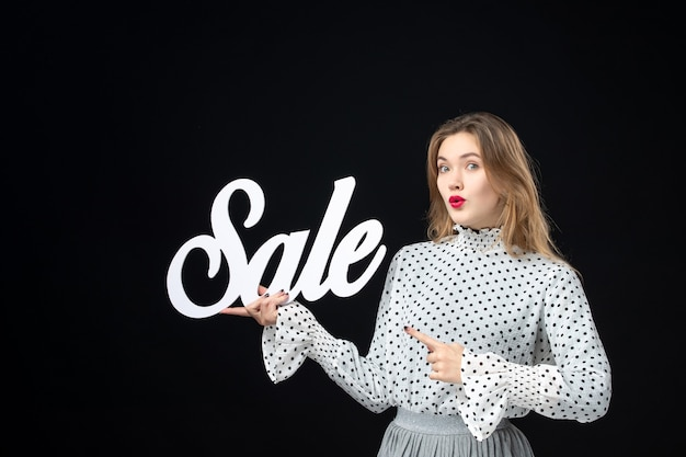 Front view young pretty female holding sale writing on black wall model shopping beauty fashion color