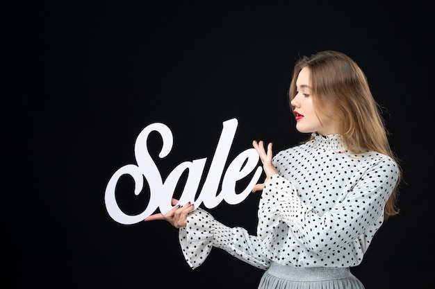 Front view young pretty female holding sale writing on a black wall model shopping beauty fashion emotion color