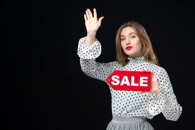 Vista frontale giovane bella donna che tiene vendita scritta sul muro nero colore rosso shopping foto emozione moda donna