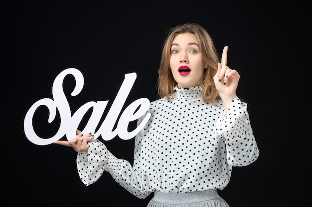 Front view young pretty female holding sale writing on black wall shopping beauty emotion color model fashion