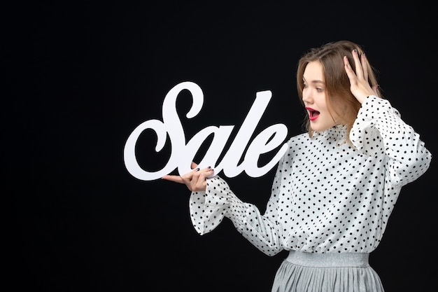 Front view young pretty female holding sale writing on the black wall shopping beauty emotion color model photo fashion